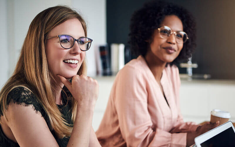 Smiling business women listening in meeting