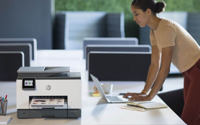 Woman using HP OfficeJet all-in-one-printer in office
