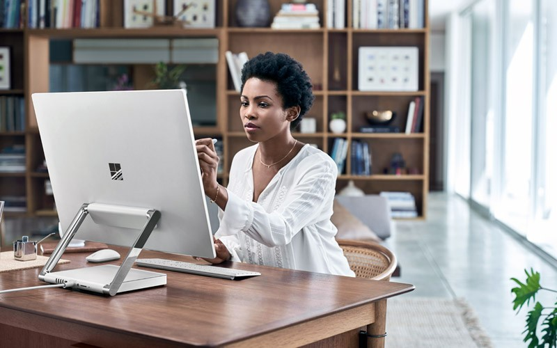 Woman working remotely in home office using Surface Studio